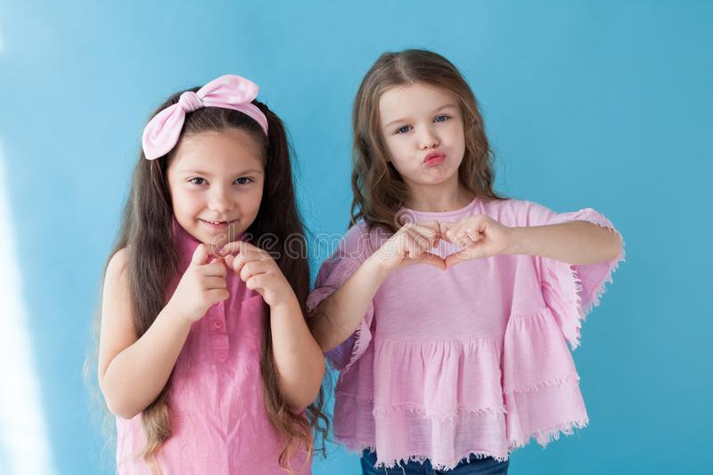 Two little girls are sisters girlfriends in a pink dress royalty free stock images