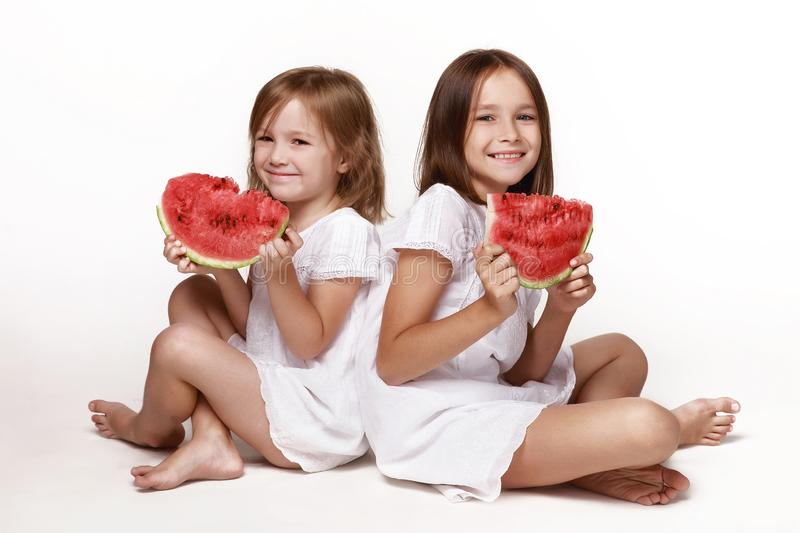 Two little girls, sisters, sit in the studio on a white background with pieces of watermelon. In bright clothes, barefoot. royalty free stock photo