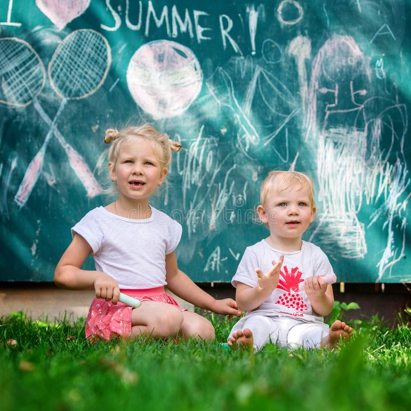 Two little girls sit on the grass and play school in the garden. Girls on the background of the green board, which says royalty free stock images