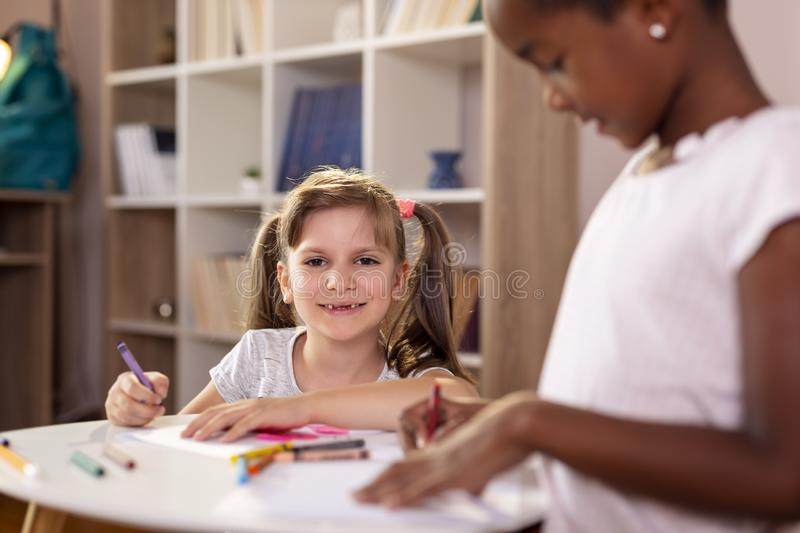 Girls drawing with crayons stock image