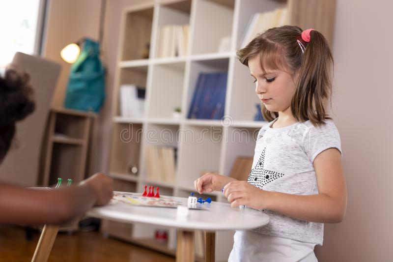 Little girls playing ludo board game stock photography