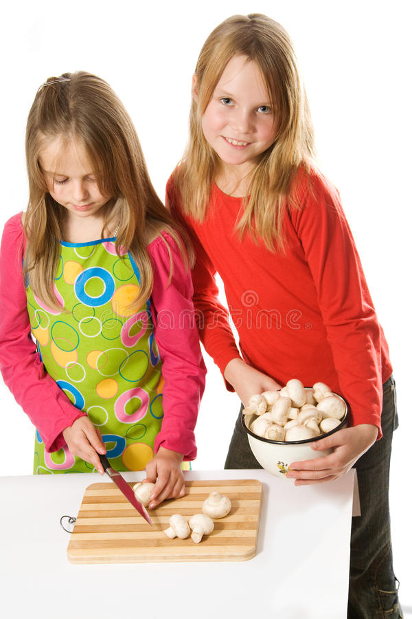 Two little girls slicing mushrooms royalty free stock photo