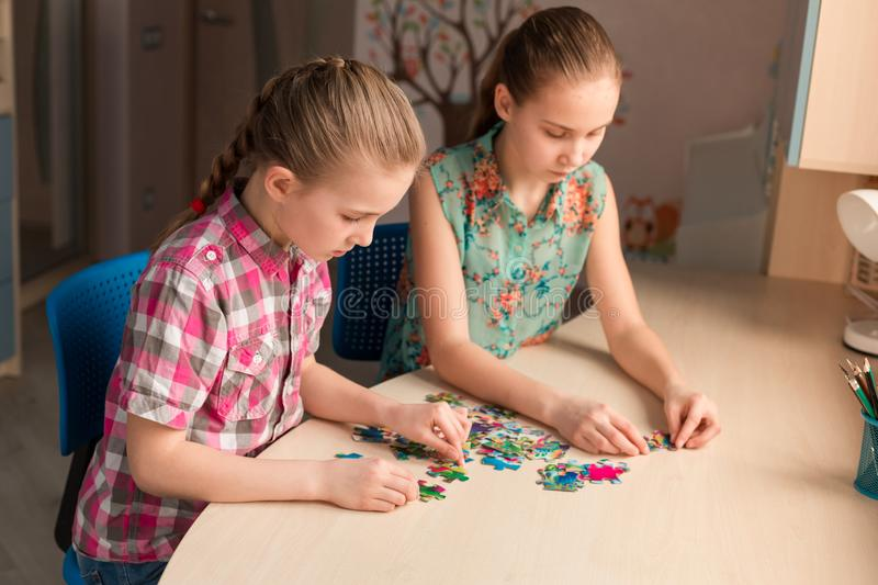 Two little girls solving puzzle together stock photography