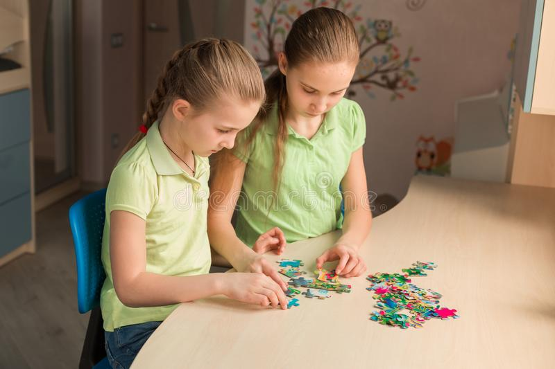 Two little girls solving puzzle together royalty free stock photo