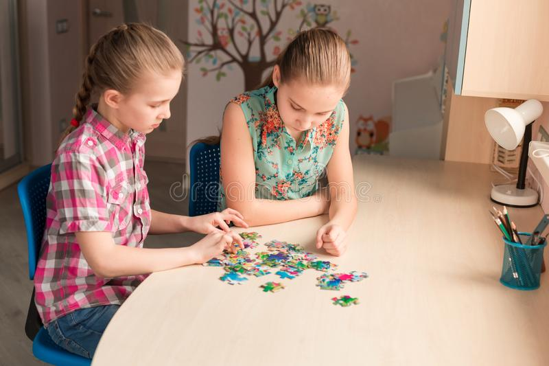 Two little girls solving puzzle together royalty free stock images
