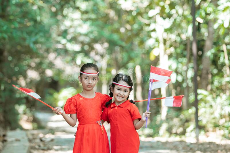 Two little girls standing in red shirt and red and white attribute holding red and white flags stock photo