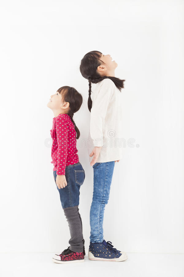 Two little girls standing together and looking up royalty free stock photo