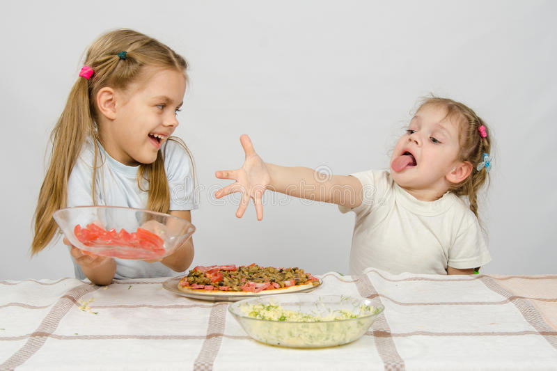 Two little girls at a table prepared pizza royalty free stock photography