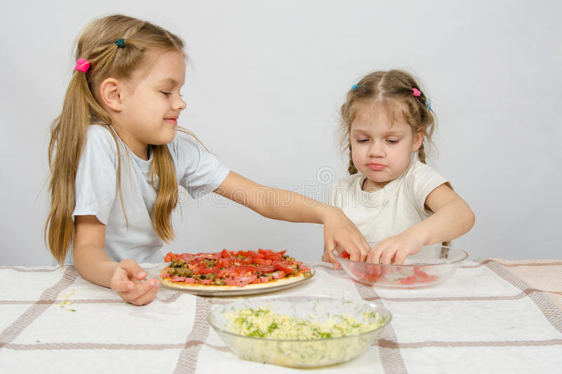 Two little girls at the table spread on tomato pizza stock photography