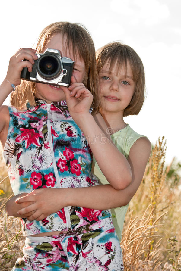 Two little girls taking picture with SLR camera royalty free stock photos