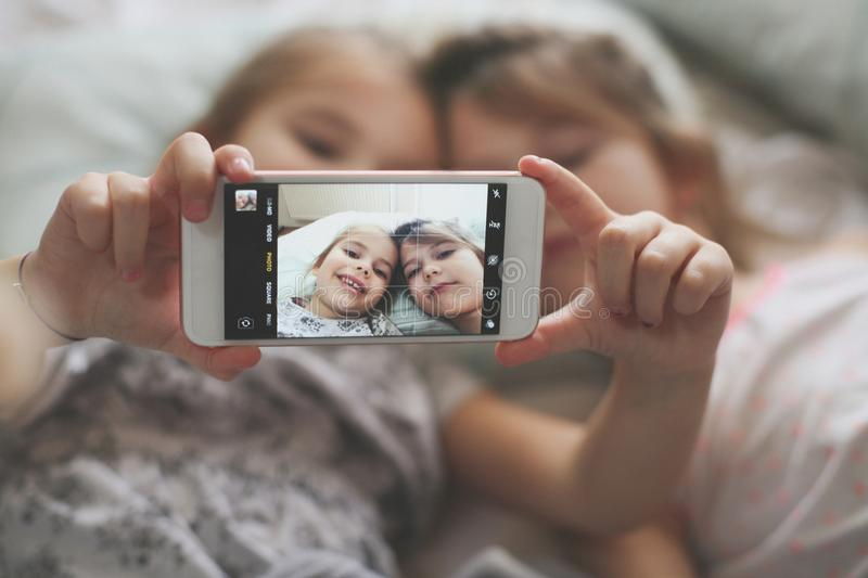 Self picture in bed. Two little girls taking self picture in bed. Space for copy. Focus is on hands. Close up stock photography