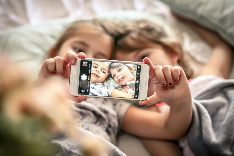 Self portrait in bed. Two little girls taking self picture in bed. Space for copy. Focus is on hands. Close up royalty free stock photos