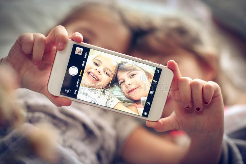 Self time in bed. Two little girls taking self picture in bed. Space for copy. Focus is on hands. Close up royalty free stock images