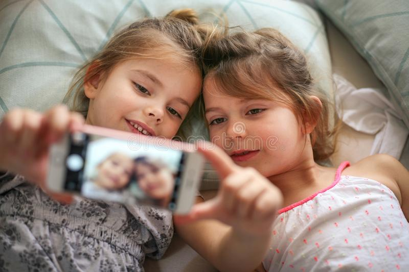 Self time in bed. Two little girls taking self picture in bed. Space for copy. Focus is on little girls. Close up stock photo