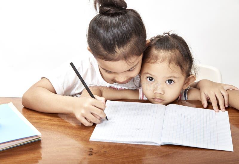 Two little girls thai homework royalty free stock images