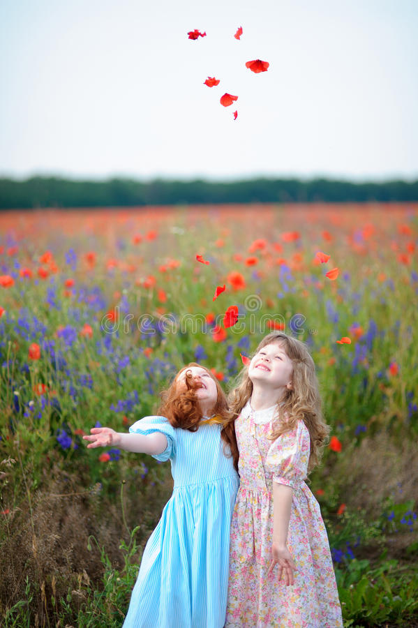 Two little girls throw petals of wildflowers stock photos