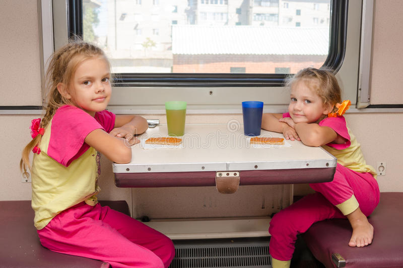 Two little girls on train sitting at the table in the outboard second-class car in the same clothes. Two little girls on the train sitting at the table in the royalty free stock photos
