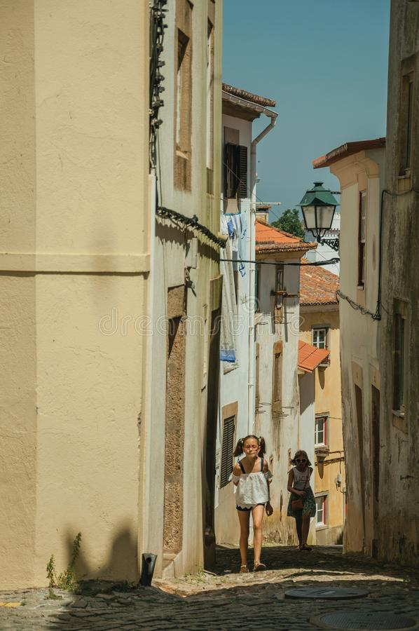 Two little girls walking up the alley on slope with old houses royalty free stock images