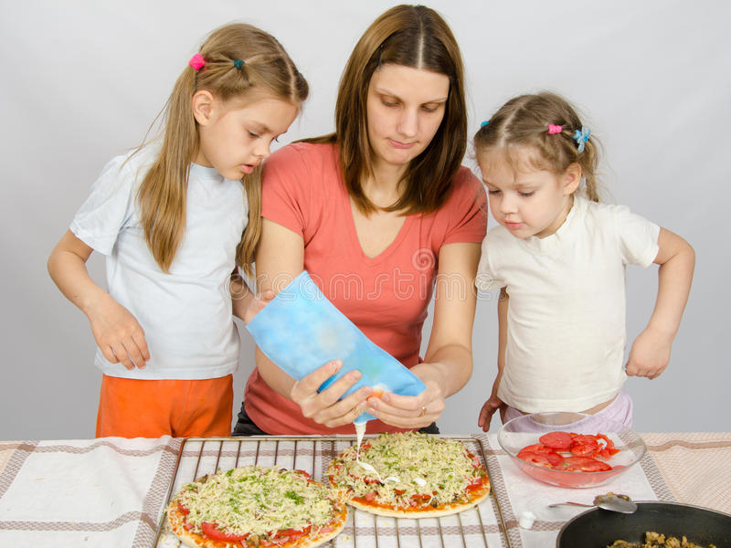 Two little girls are watching with interest as mother is watering mayonnaise pizza stock photo