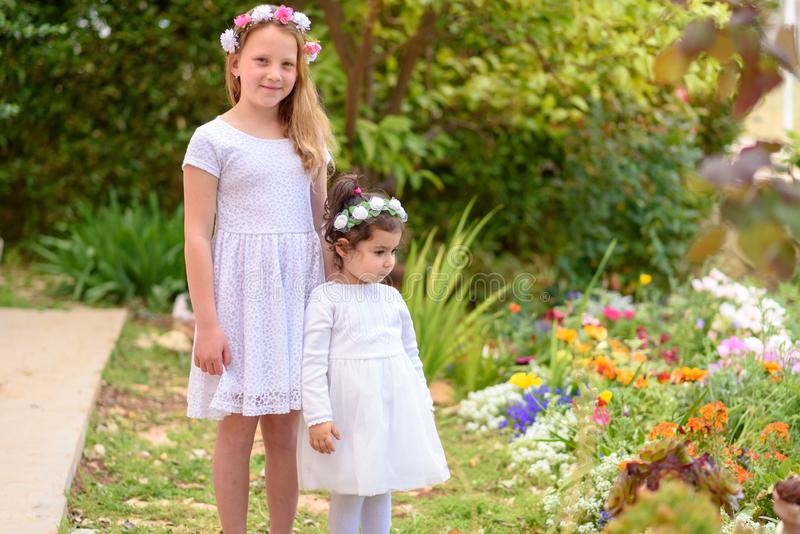 Two little girls in white dresses and flower wreath having fun a summer garden. Outdoor portrait of two cute little girls. Beautiful children witn white dresses royalty free stock images