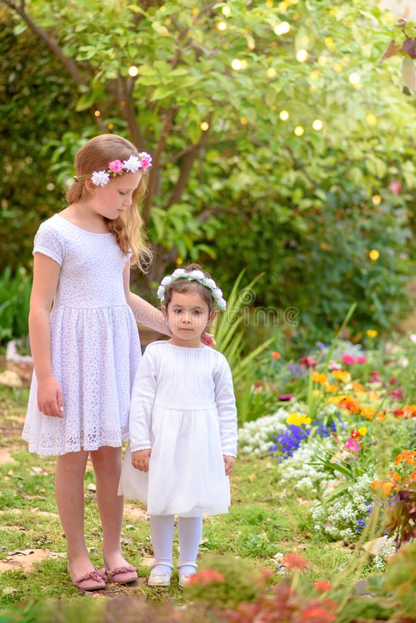 Two little girls in white dresses and flower wreath having fun a summer garden. Outdoor portrait of two cute little girls. Beautiful children witn white dresses royalty free stock photos