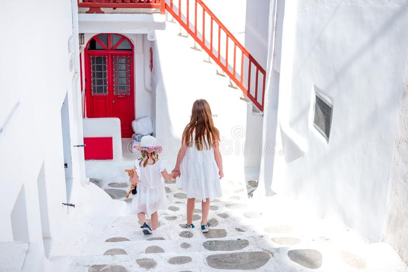 Two little girls holding hands white walking down narrow Greek streets royalty free stock photography