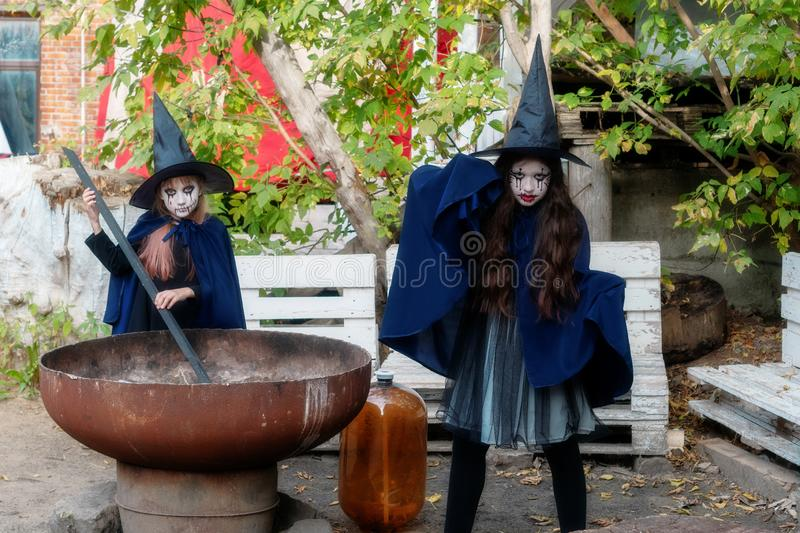 Two little girls in witch costumes brew a magic drink in an abandoned old building. Halloween concept stock photos