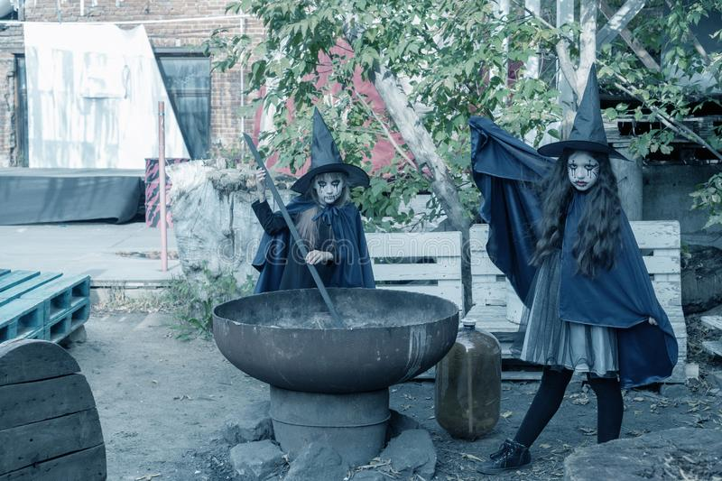 Two little girls in witch costumes brew a magic drink in an abandoned old building. Halloween concept. Toned royalty free stock photography