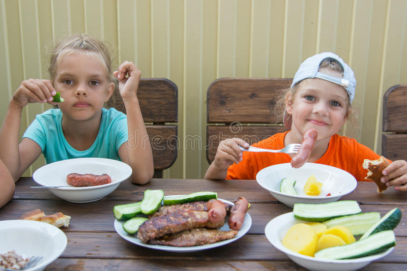 Two little girls at wooden table in nature eating grilled sausages stock photo