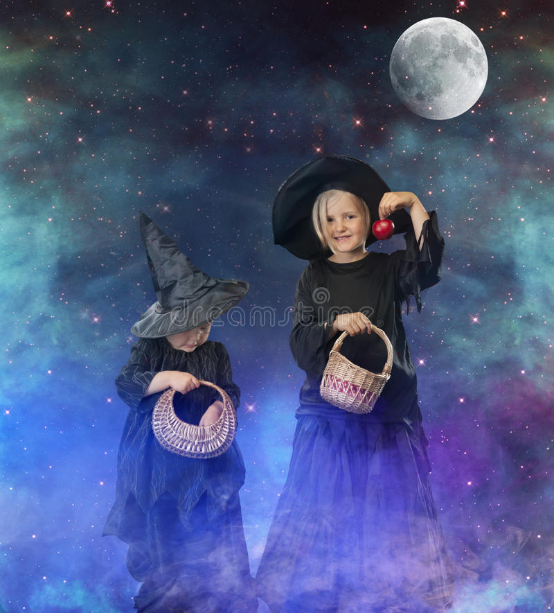 Two little halloween witches at night, with stars and moon royalty free stock photography