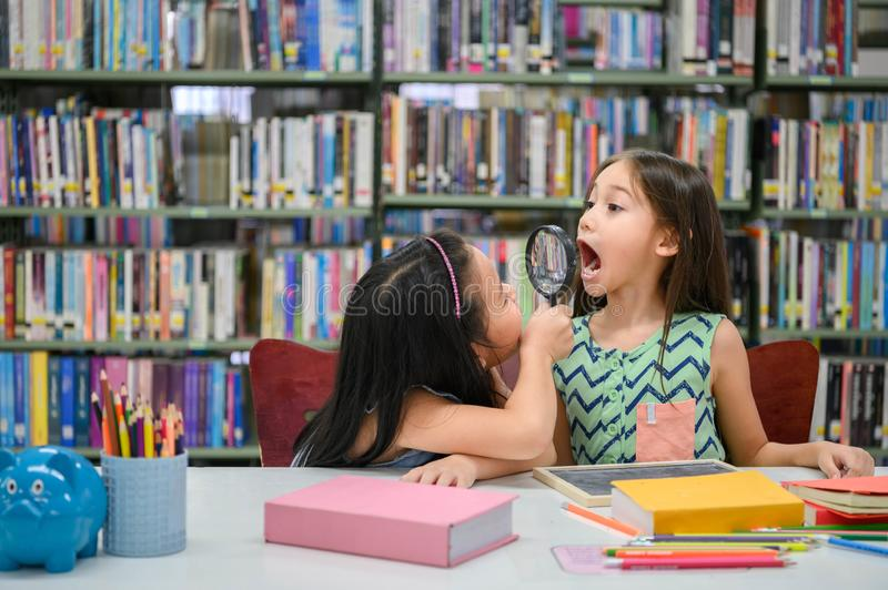 Two little happy cute girls making funny face and playing together in library at school as dental health check. Education and self royalty free stock images