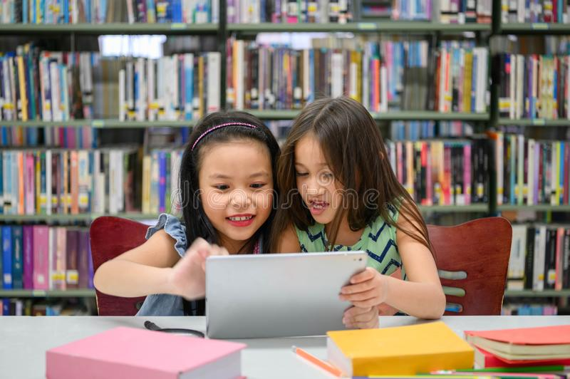 Two little happy cute girls playing on a tablet PC computing device in library at school. Education and self learning wireless royalty free stock images