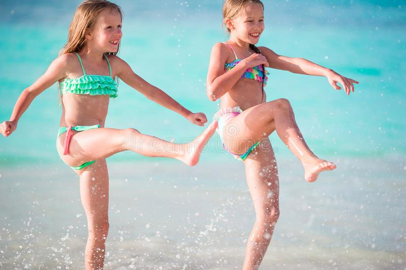 Two little happy girls have a lot of fun at tropical beach playing together at shallow water. Kids splashing. Ttle girls having fun at tropical beach playing stock image