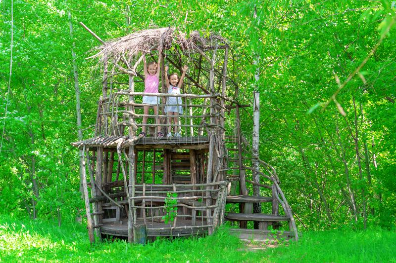 Two little happy girls in a wooden tree house on a sunny day. Sisters rejoice in the summer royalty free stock photos