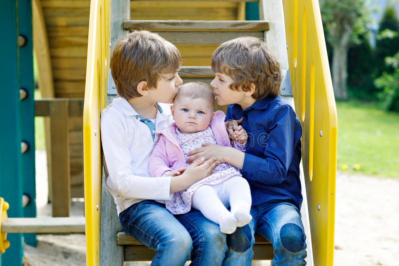 Two little happy kid boys with newborn baby girl, cute sister. Siblings on playground in summer or spring on mother`s day. Brother holding baby girl on arm stock photography