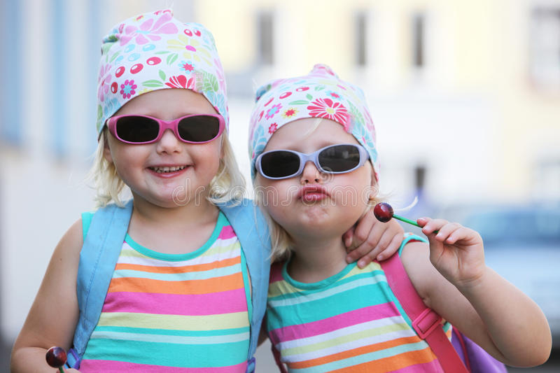 Two little identical twins in sunglasses. Two little identical twin girls with their blond hair tied up in bandannas and wearing sunglasses smiling happily at royalty free stock image