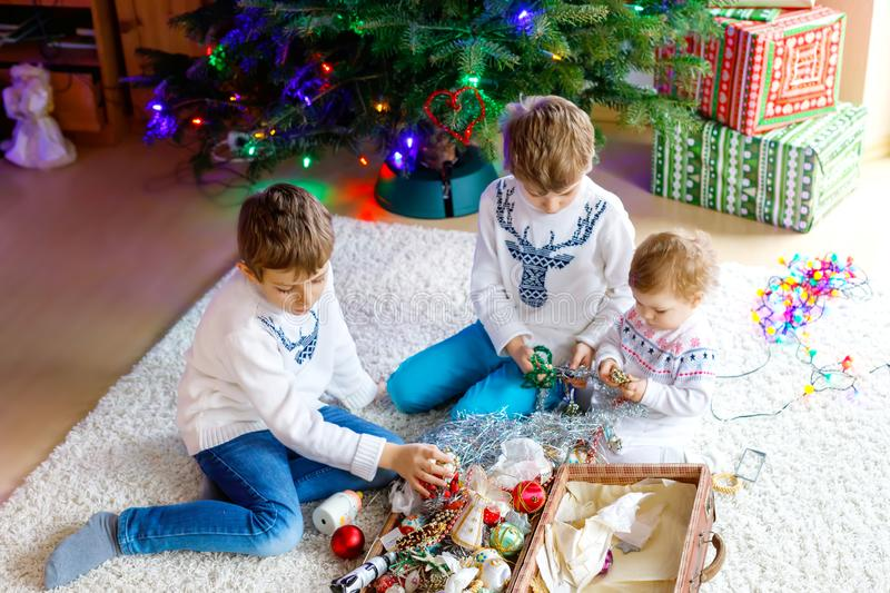 Two little kid boys and adorable baby girl decorating Christmas tree with old vintage toys and balls. Family preaparation celebration of family feast. Children stock photo