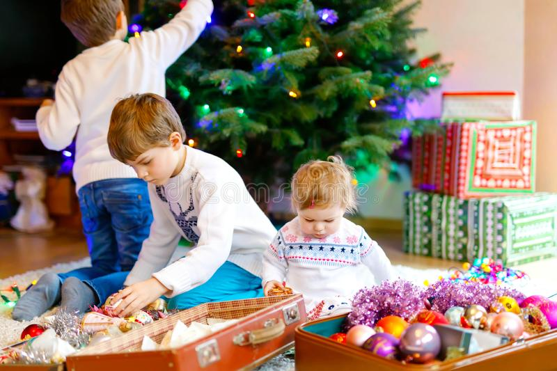 Two little kid boys and adorable baby girl decorating Christmas tree with old vintage toys and balls. Family preaparation celebration of family feast. Children royalty free stock image