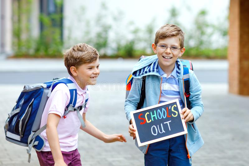 Two little kid boys with backpack or satchel. Schoolkids on the way to school. Healthy children, brothers and best stock photo