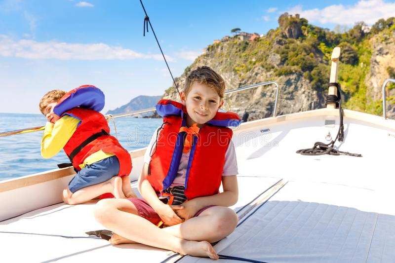 Two little kid boys, best friends enjoying sailing boat trip. Family vacations on ocean or sea on sunny day. Children stock images