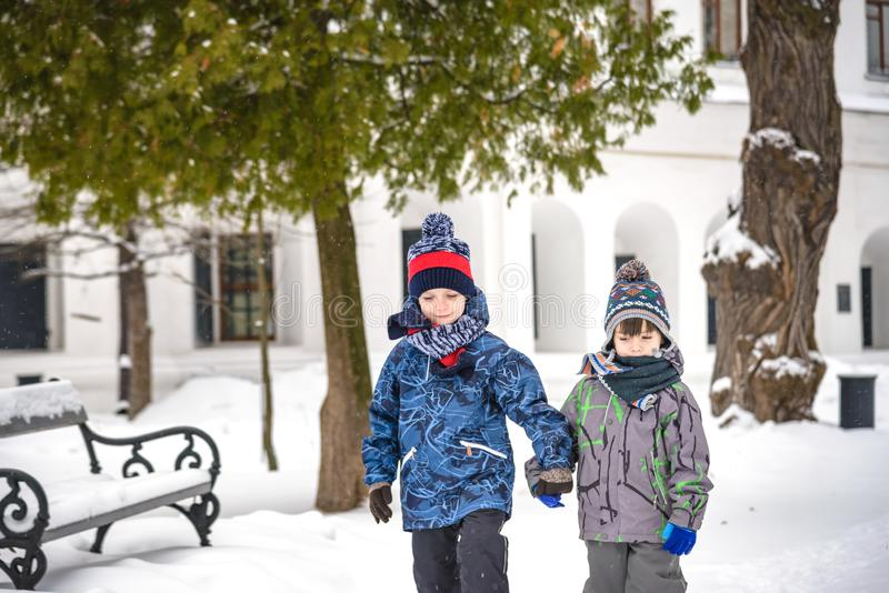 Two little kid boys in colorful clothes, outdoors during snowfall. Active outdoors leisure with children in winter on cold snowy stock photo