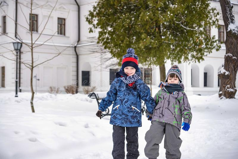 Two little kid boys in colorful clothes, outdoors during snowfall. Active outdoors leisure with children in winter on cold snowy royalty free stock image