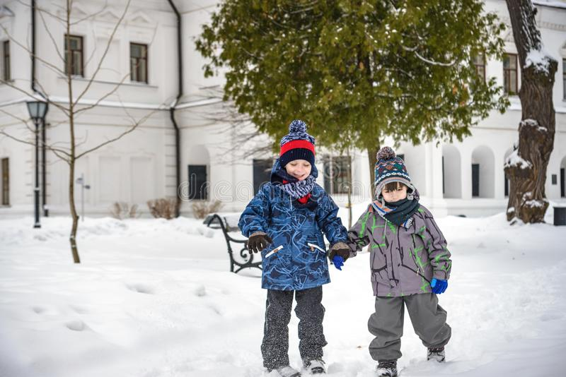 Two little kid boys in colorful clothes, outdoors during snowfall. Active outdoors leisure with children in winter on cold snowy stock images