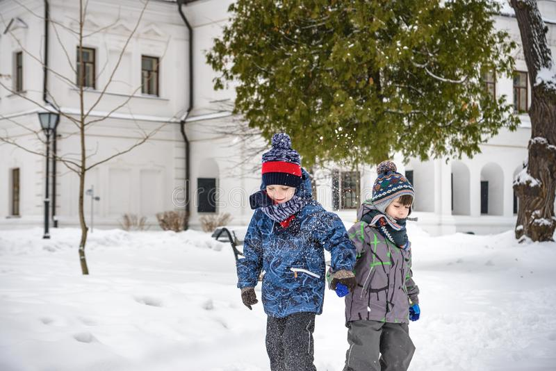 Two little kid boys in colorful clothes, outdoors during snowfall. Active outdoors leisure with children in winter on cold snowy stock image
