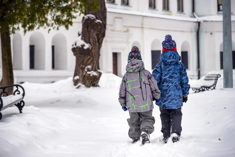 Two little kid boys in colorful clothes, outdoors during snowfall. Active outdoors leisure with children in winter on cold snowy royalty free stock photography