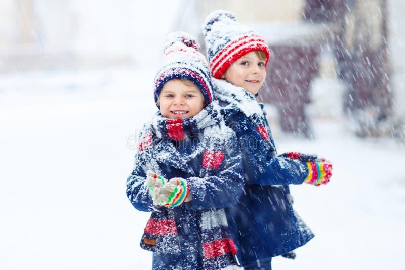 Happy children having fun with snow in winter stock photo