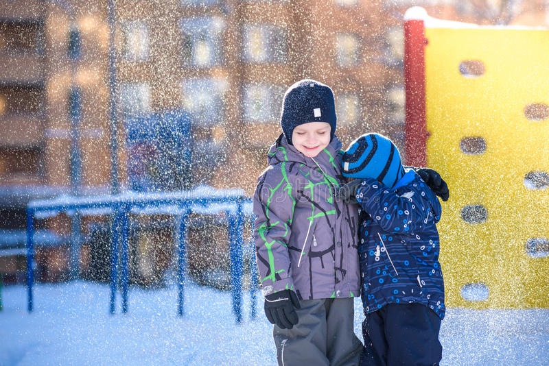 Two little kid boys in colorful clothes playing outdoors during snowfall. Active leisure with children in winter on cold days. Hap. Py siblings and twins having stock image