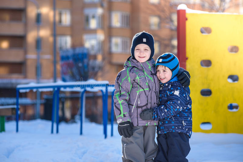 Two little kid boys in colorful clothes playing outdoors during snowfall. Active leisure with children in winter on cold days. Hap. Py siblings and twins having stock images