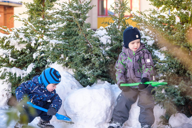 Two little kid boys in colorful clothes playing outdoors during snowfall. Active leisure with children in winter on cold days. Hap. Py siblings and twins having stock photo
