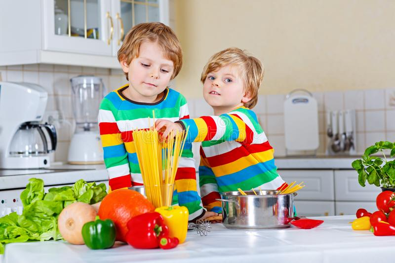 Two little kid boys cooking pasta with vegetables stock photos